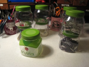 Truvia container with label. Then naked containers with baubles inside. Like my jewelry tools mug holders?